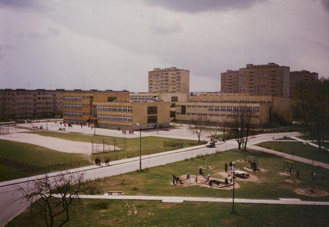 Zdjęcie przedstawia budynek szkoły, boiska oraz plac zabaw. W tle widać bloki mieszkalne.