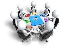 Grafika przedstawiająca grupę ludzików siedzącą przy stole i układającą puzzle.