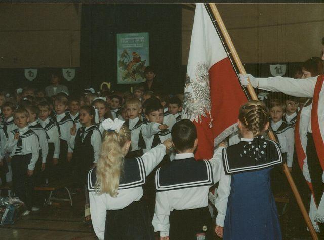 Uroczystość ślubowania klas I. Kilkoro uczniów trzyma dłonie skierowane w stronę sztandaru, pozostali stoją w rzędach.
