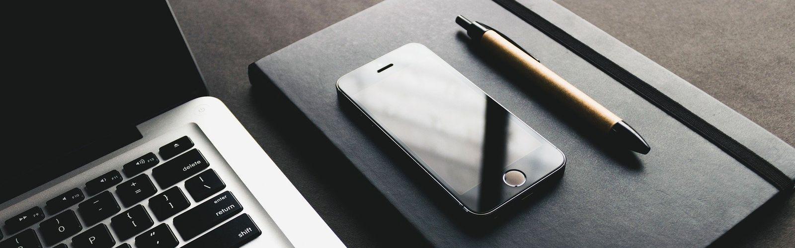 Zdjęcie przedstawia komputer, notatnik, telefon oraz długopis.