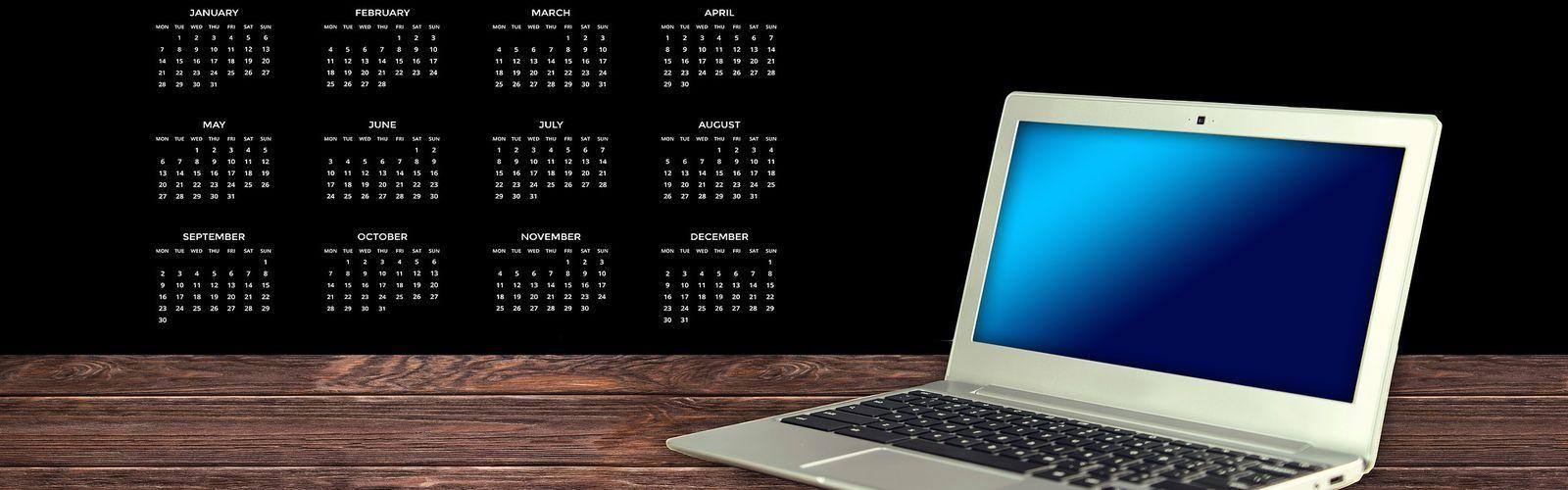 Grafika przedstawia kalendarz - biały na czarnym tle. Po prawej stronie znajduje się laptop oraz drewniana podłoga.