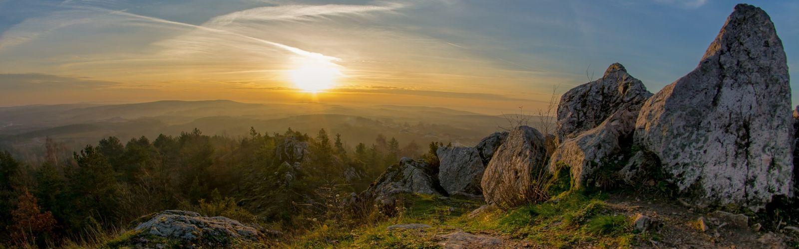 Zdjęcie przedstawia wschód słońca, lasy, skały.