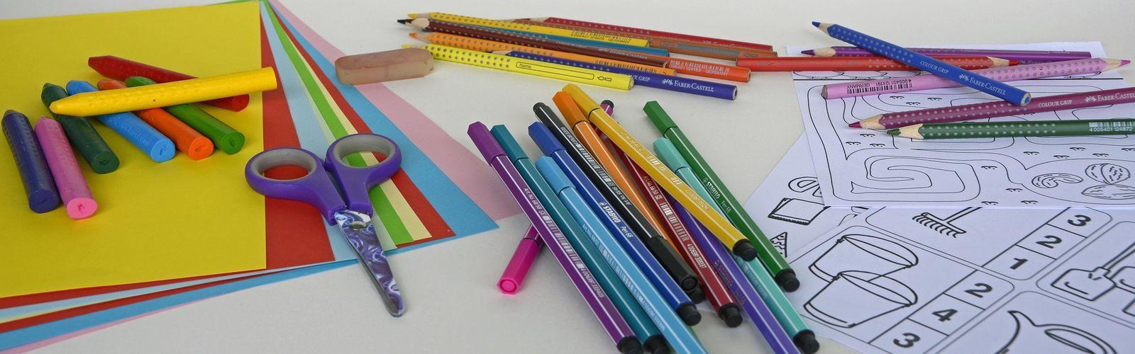 Grafika przedstawia przybory szkolne: kolorowy papier, na którym leżą kredki świecowe, nożyczki. Na środku jest garść cienkopisów, z kolei po prawej stronie kolorowanki, na których leżą kredki.