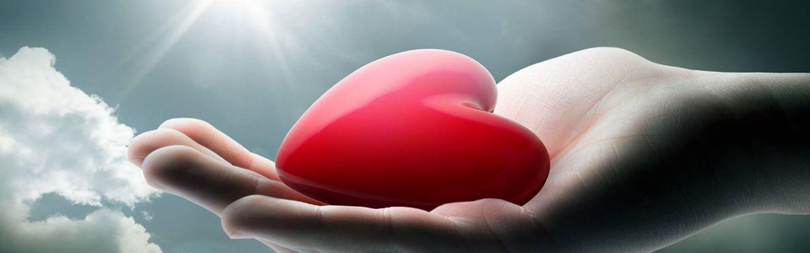 Czerwone serce leży na otwartej dłoni. W tle widać niebo, chmury oraz promienie słońca.