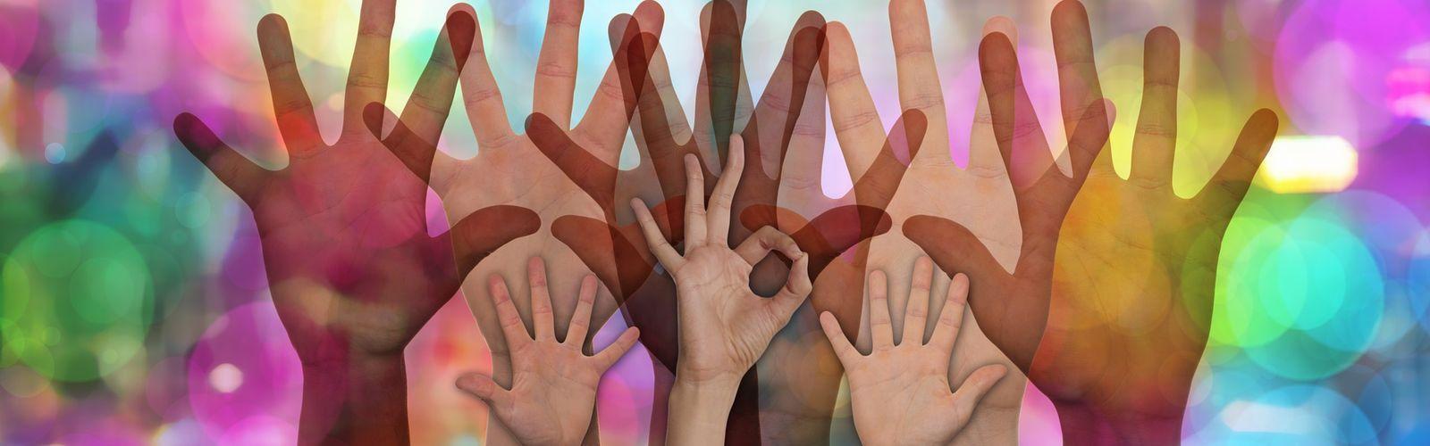 Grafika przedstawia dłonie dorosłych oraz dzieci. Tło jest bardzo kolorowe.