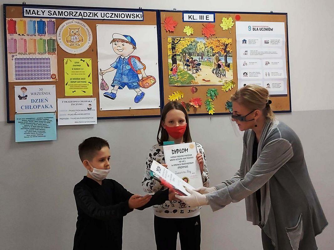 Uczniowie z klasy 3a odbierają dyplomy i nagrody książkowe