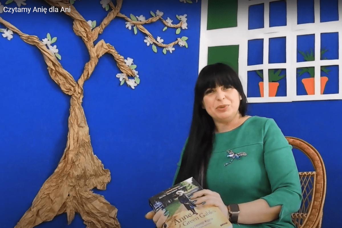 """Pani dyr. Marta Dobrowolska-Wesołowska z książką """"Ania z Zielonego Wzgórza"""" na tle dekoracji przedstawiającej dom Ani Shirley, obok stoi drzewo."""