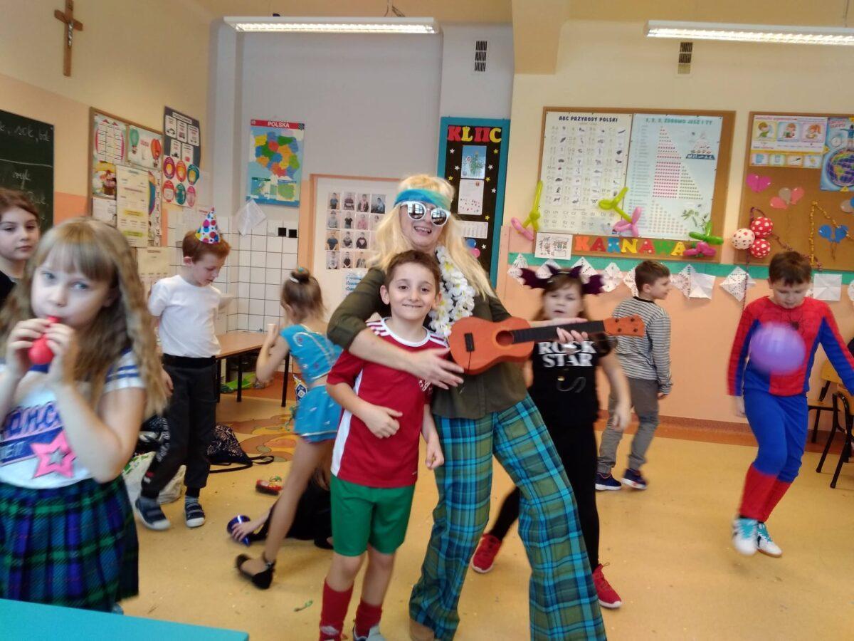 Uczeń przebrany za piłkarza pozuje do zdjęcia z wychowawczynią przebraną za hipisa. Nauczycielka w ręce trzyma ukulele.