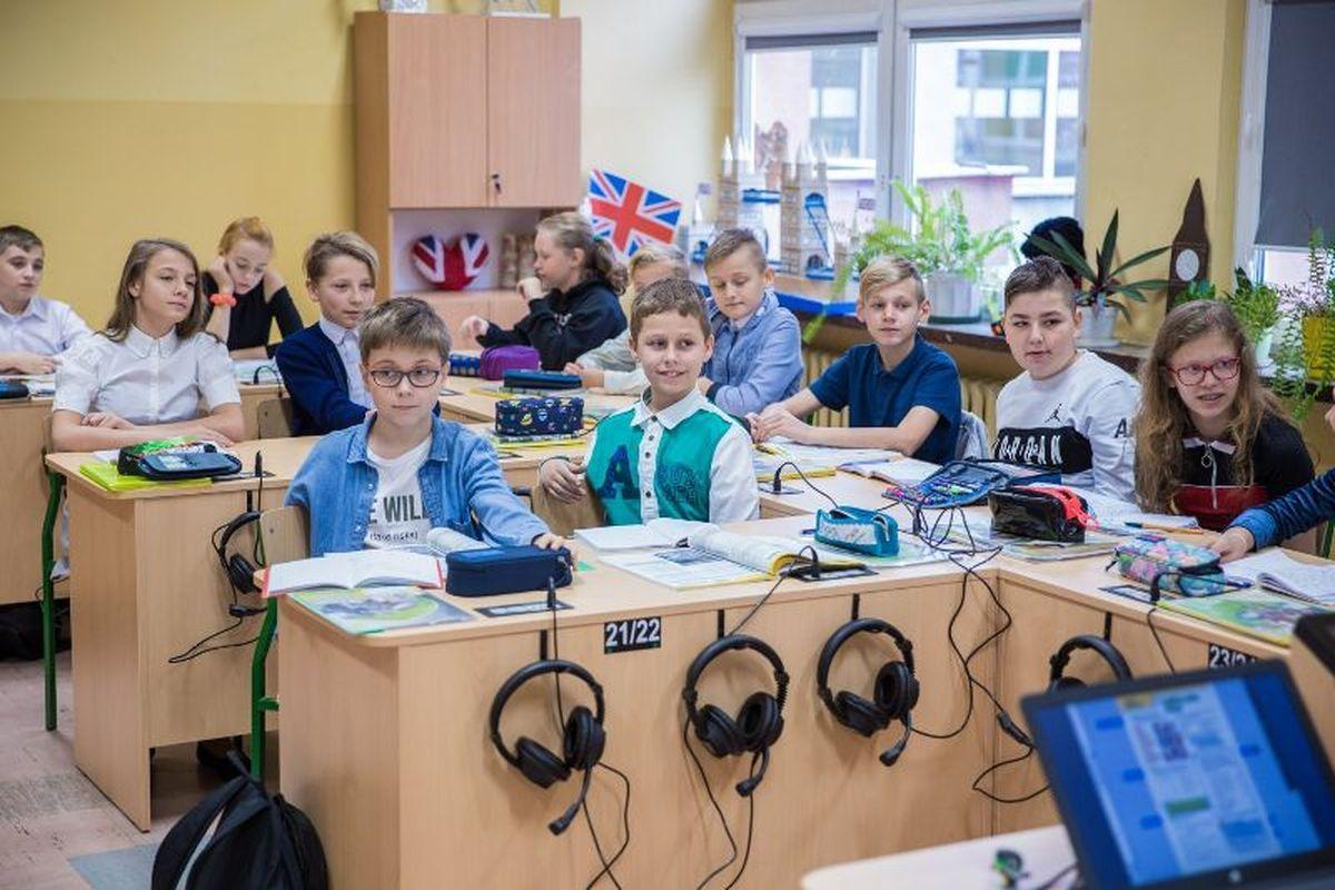Uczniowie siedzą w nowoczesnej pracowni języka angielskiego.