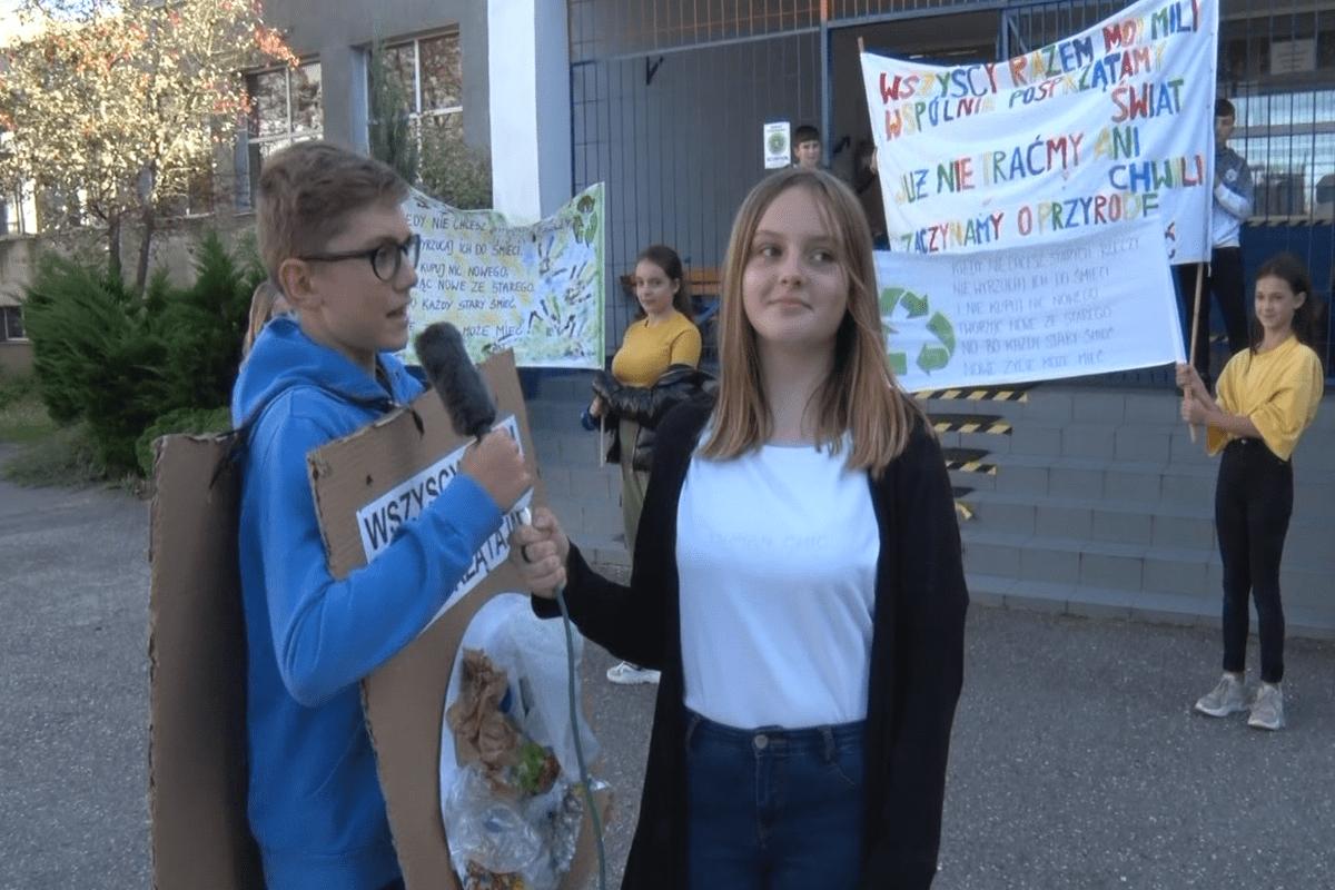 Uczniowie klasy 7e podczas kręcenia ekologicznego filmu stoją przed szkolą z transparentami.