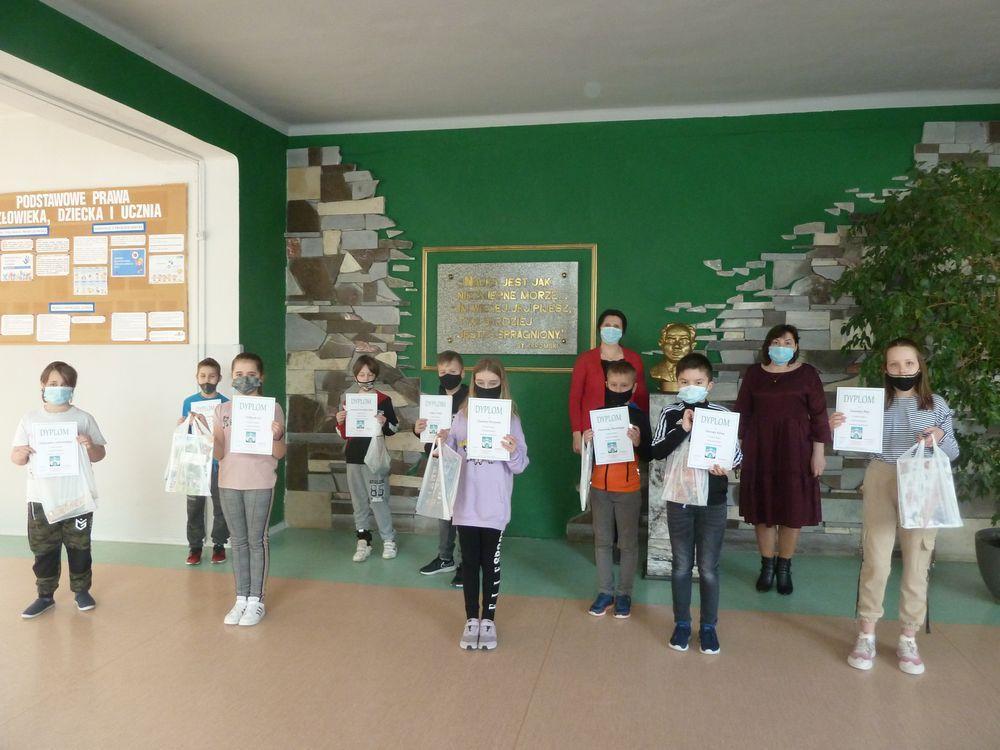 Nagrodzeni uczniowie prezentują dyplomy na korytarzu szkolnym.