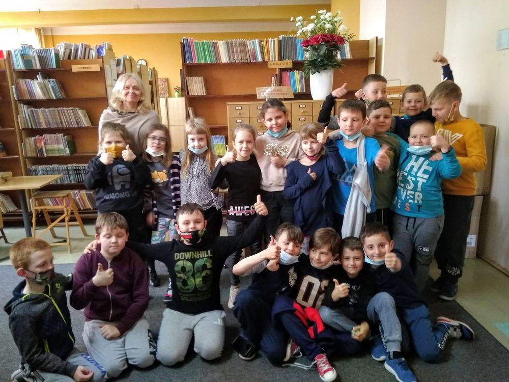 Uczniowie klasy 2c oraz pani bibliotekarka stoją na tle regałów z książkami,pozują do zdjęcia, trzymają kciuki w górze, uśmiechają się.