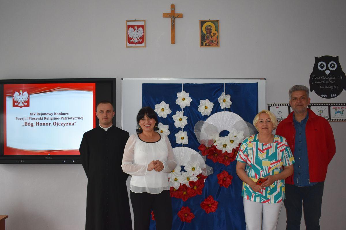 Jury konkursu Bóg, Honor, Ojczyzna na tle dekoracji patriotycznej, białych i czerwonych kwiatów.