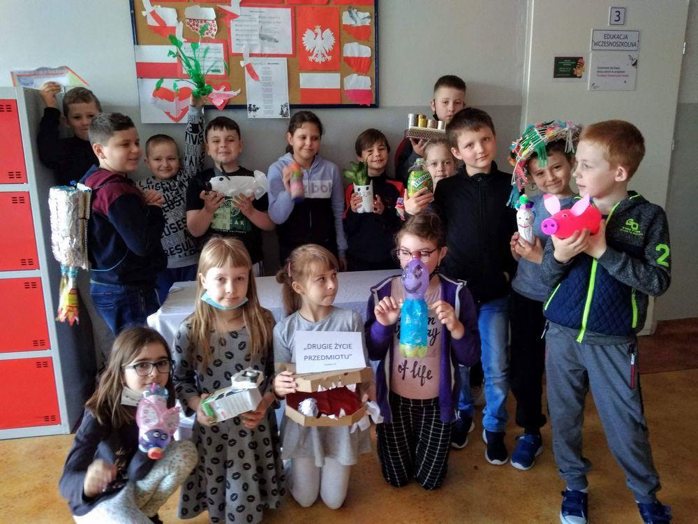 Dzieci z 2c trzymają w rękach przedmioty, które wykonały z plastikowych butelek, zakrętek, kartonów itp.