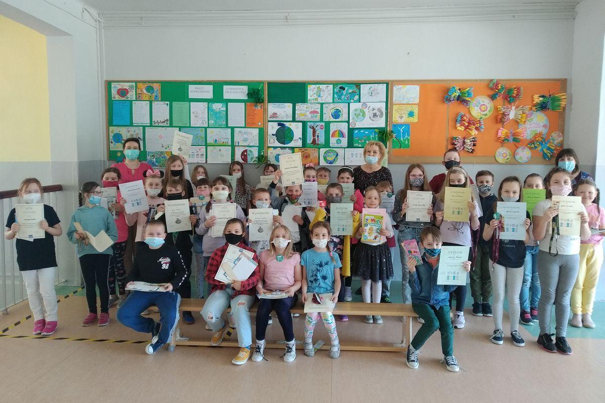 Zdjęcie , na którym znajdują się uczniowie biorący udział w konkursach ekologicznych wraz z wicedyrektor i organizatorami konkursu