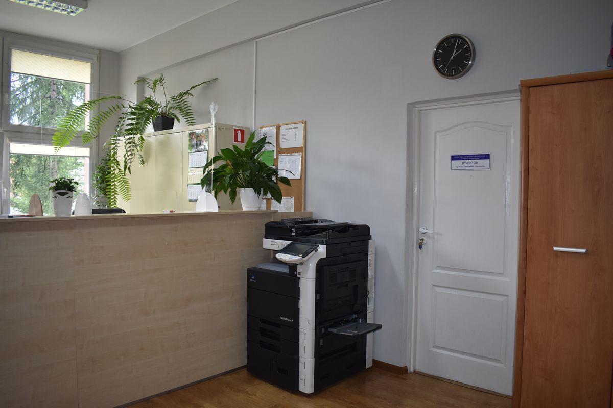 Zdjęcie przedstawia sekretariat wewnątrz. Na wprost widoczna lada. Z prawej strony są drzwi do gabinetu pani dyrektor.