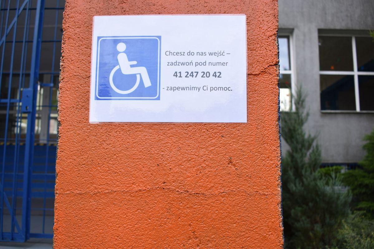 Zdjęcie przedstawia oznakowaną tabliczkę dla osób niepełnosprawnych ruchowo z numerem telefonu.