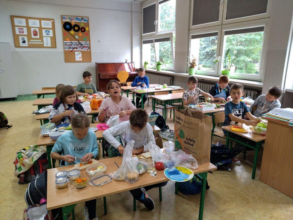 """Uczniowie klasy III c przy kulinarnej pracy. Dzieci przygotowują sałatkę warzywną i kolorowe , zdrowe kanapki na drugie śniadanie. W tle sali widać pianino i tablicę z napisem """" Muzyka jest w nas"""""""