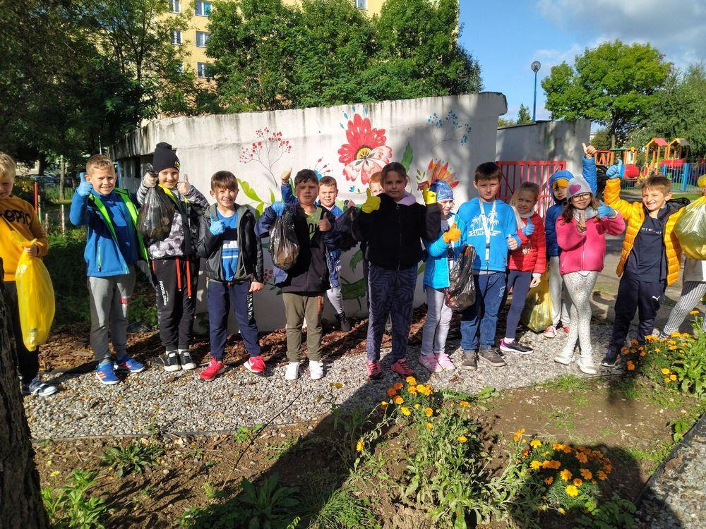 Uczniowie klasy III c stoją na tle szkolnego śmietnika, ozdobionego pięknymi, kolorowymi kwiatami. Uśmiechają się po udanej akcji sprzątania świata.