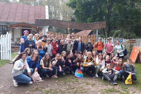Zbiorowe zdjęcie uczestników wycieczki z nauczycielami. W tle widać napis Brzozowe Wzgórze.