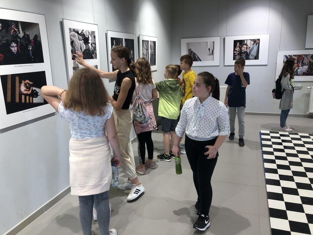 Grupa uczniów patrzy na ścianę galerii gdzie wiszą zwycięskie prace w konkursie fotograficznym