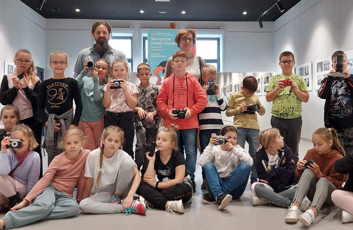 Uczniowie wraz z kustoszem i wychowawczynią (stoją lub siedzą) w sali na tle plakatu informującego o wystawie. Niektórzy trzymają dawniejsze aparaty fotograficzne. W tle, na ścianach wiszą nagrodzone i wyróżnione zdjęcia konkursowe.