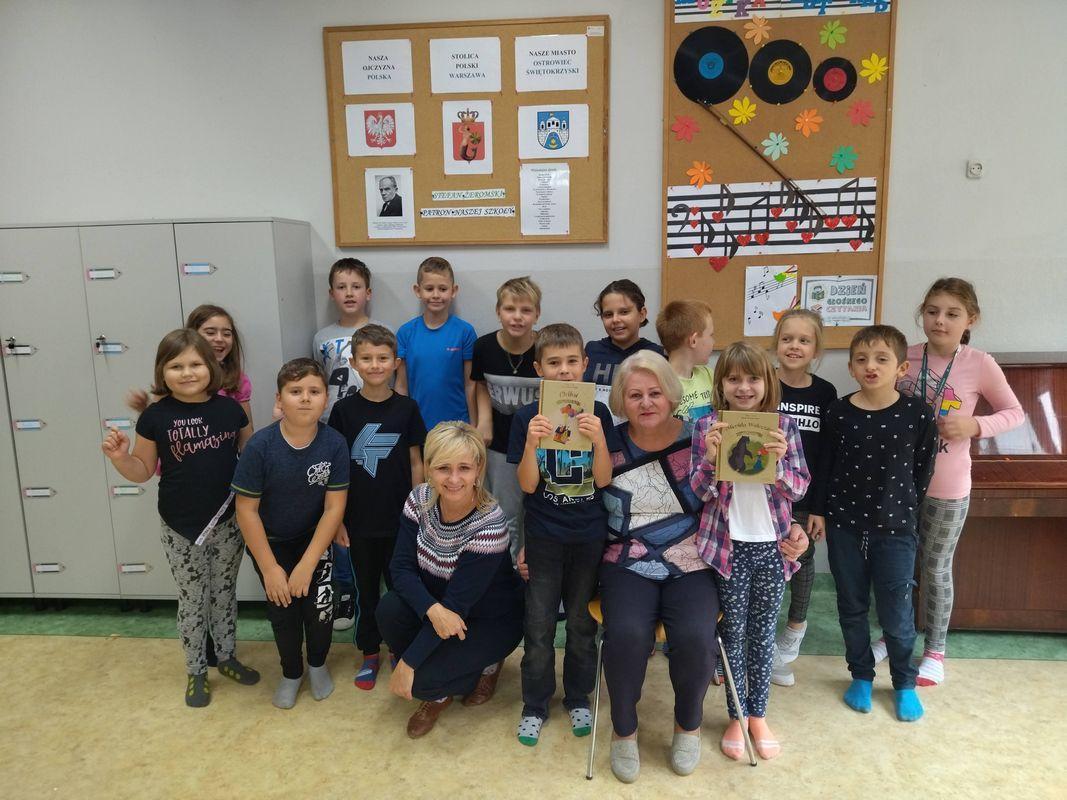 Uśmiechnięci uczniowie z klasy 3c pozują do zdjęcia z panią Elą- babcią Adama oraz wychowawcą klasy.